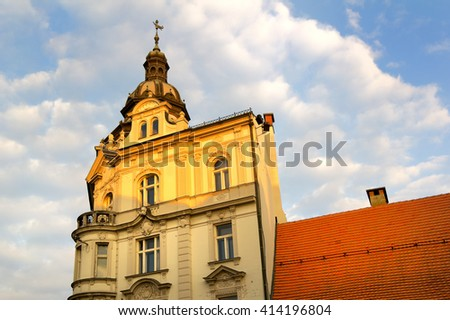 Mestna Hranilnica, Maribor, Slovenia. Beautiful neo-baroque bulding on Grajski trg (Castle square). Facade of building is lit by yellow light during sunset. Copy space - stock photo