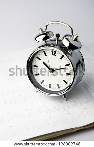 Metal Alarm clock with diary on isolate white background - stock photo