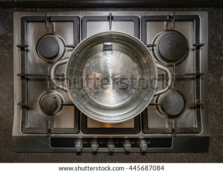 Metal aluminum pan on traditional iron stove cooker boiling water for cooking pasta - stock photo