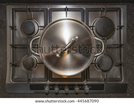 Metal aluminum pan with closed lid on traditional iron stove cooker boiling water for cooking pasta - stock photo