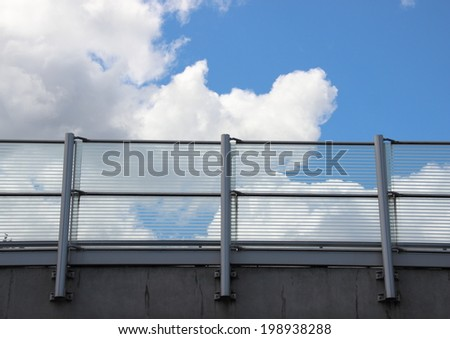Metal and glass railing with blue sky horizontal
