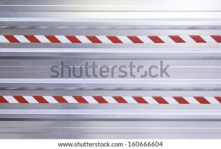 Metal background with warning sign, detail of a metal wall with hazard information - stock photo