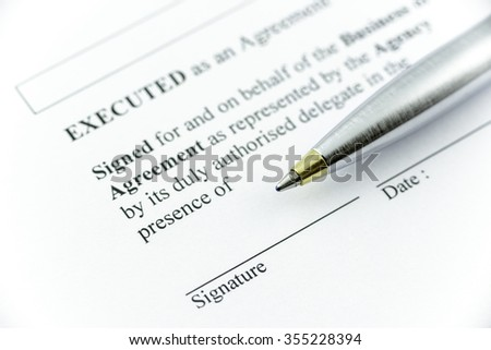 Metal ballpoint pen on an agreement, preparation for signing an agreement. - stock photo