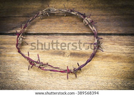 metal Barbed Wire made like the crown of thorns of Jesus om wooden  background, can be used for Christian concept , Easter concept, Copy space - stock photo