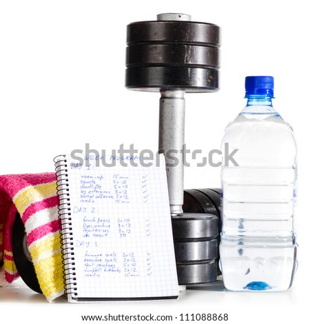 metal barbells with bottle of water, towel and week program - stock photo