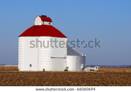 Metal barn silo in a field with blue sky and and copy space - stock photo