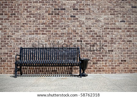 Metal bench against a brick wall - stock photo