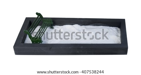 Metal Bench in an enclosed park filled with a white substance, such as snow or sand - path included  - stock photo