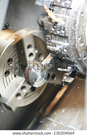metal blank machining process on lathe with cutting tool and coolant at steel manufacturing - stock photo