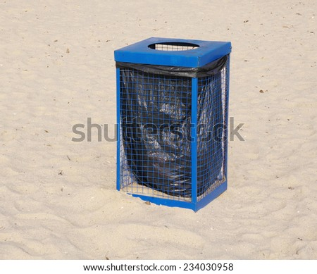Metal blue garbage dustbin on beach sand in sunny day  - stock photo