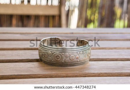 Metal bracelet on wooden table - stock photo