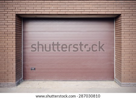 Metal brown gates of the private garage. - stock photo