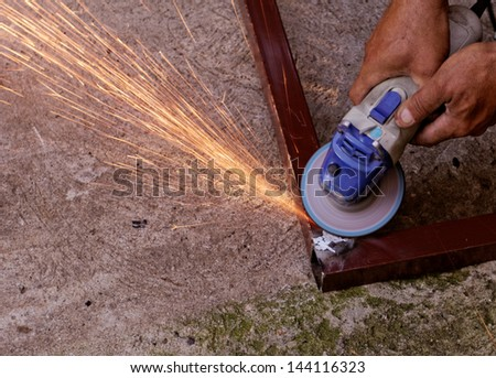 Metal buffing with hand grinder. Sparks while grinding iron.