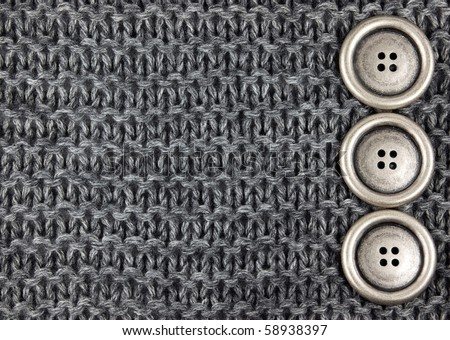 Metal buttons on a gray knitted fabric background - stock photo