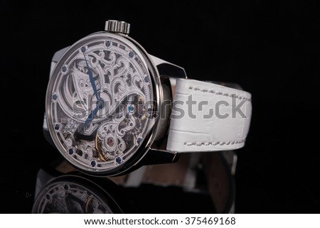 Metal case skeleton watches with blue hands and blue sapphires on white alligator leather strap front side view