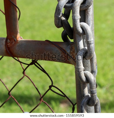 Metal chain and lock  on old rusted metal gate  used to keep a business safe at night from thieves and trespassers.