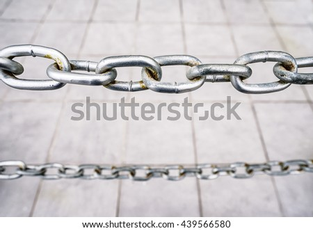 Metal chain fence against of city sidewalk