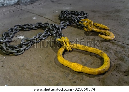 Metal chain with yellow hooks - stock photo
