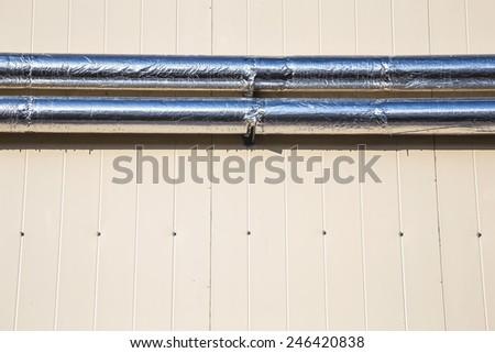 Metal chrome pipes on yellow plastic siding wall - stock photo
