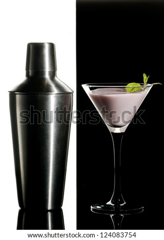 Metal cocktail shaker and cream cocktail with mint leaves on a black and white  background - stock photo