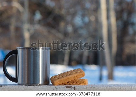 Metal coffee cup tea cup with classic shortbread butter cookies on a winter background