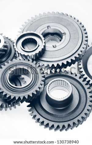 Metal cog gears bonding together on plain background - stock photo