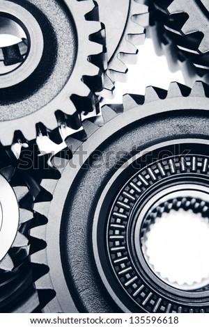Metal cog wheels bonding together - stock photo