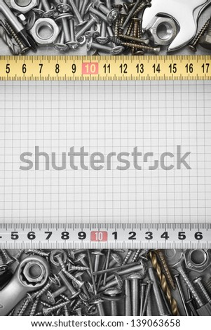 metal construction  hardware tool on checked paper - stock photo
