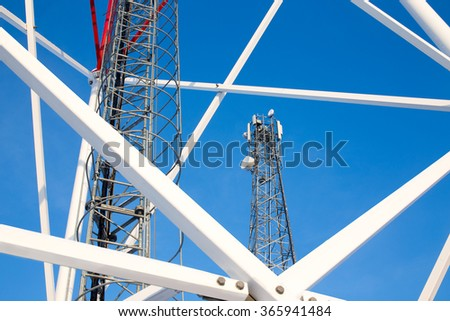 metal construction telecommunications tower against a blue sky. ladder, support towers and metal structures cell tower closeup