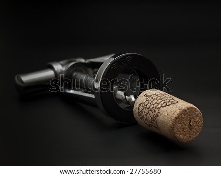 metal corkscrew with cork on the black background - stock photo