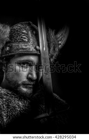 Metal, Costume, Viking warrior with a huge sword and helmet with horns - stock photo