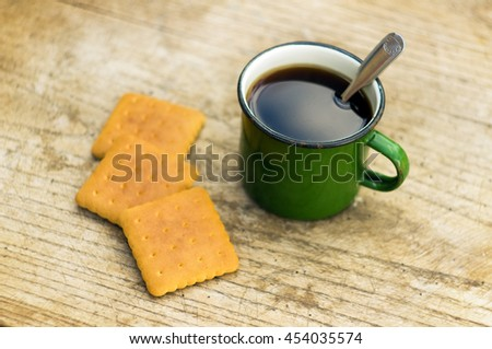 metal cup of tea with cookies on wooden background - stock photo
