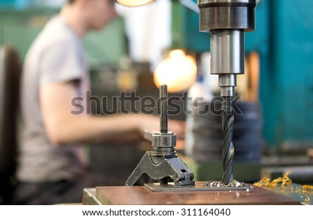 metal cutting hole boring on vertical drilling machine with machining drill tool at factory workshop background - stock photo