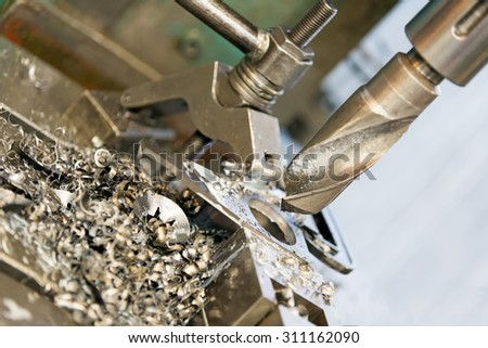 metal cutting hole boring with machining drill tool and shavings - stock photo