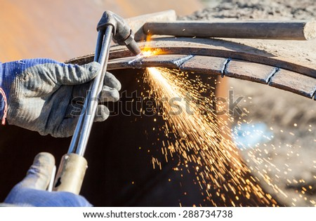 Metal cutting with a gas burner and many sparks - stock photo