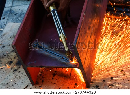 Metal Cutting With Acetylene Gas. Workman is working by use torch cut the iron in factory. Spark splash around the ground. - stock photo