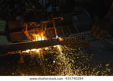 Metal cutting with acetylene torch close-up on low light