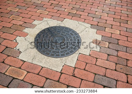 metal drain lid on brick ground street - stock photo