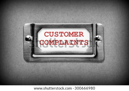 Metal drawer label for storage of Customer Complaints in red text on a white card. Processed in black and white for effect. - stock photo
