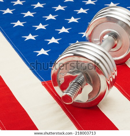 Metal dumbbell over US flag as symbol of healthy life style - studio shot - 1 to 1 ratio
