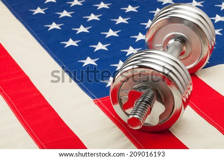 Metal dumbbells over USA flag as symbol of healthy nation