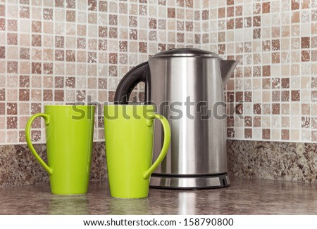 Metal electric kettle and green cups in the kitchen. - stock photo