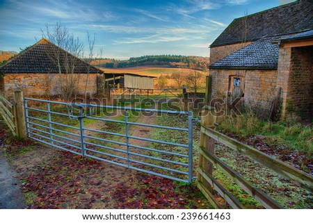 Metal farm gate leading past farm buildings to country side