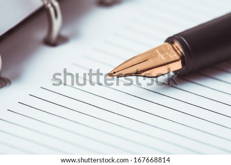 Metal feather pen on the ruled paper in the notebook