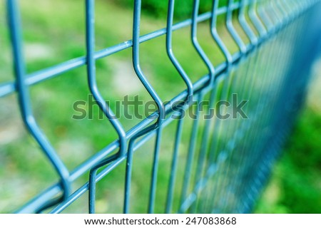 Metal fence wire, painted in blue color. - stock photo