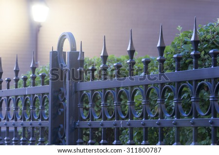 metal fence with light under green