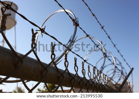 Metal fence with razor wire on top - stock photo