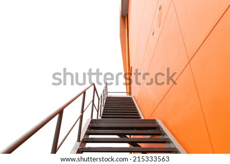 Metal fire escape or emergency exit on Orange Wall of Building With Isolated White Background