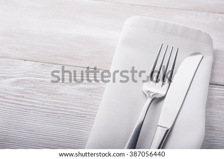 metal fork and knife on wooden table - stock photo