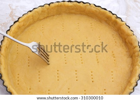 Metal fork makes holes in a raw pastry case in a metal baking tin - stock photo